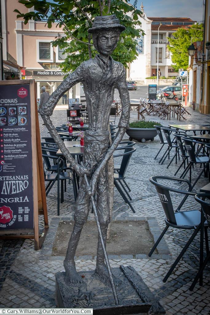 A bronze statue of a gaunt figure holding a salt panning rake in Aveiro's town centre.