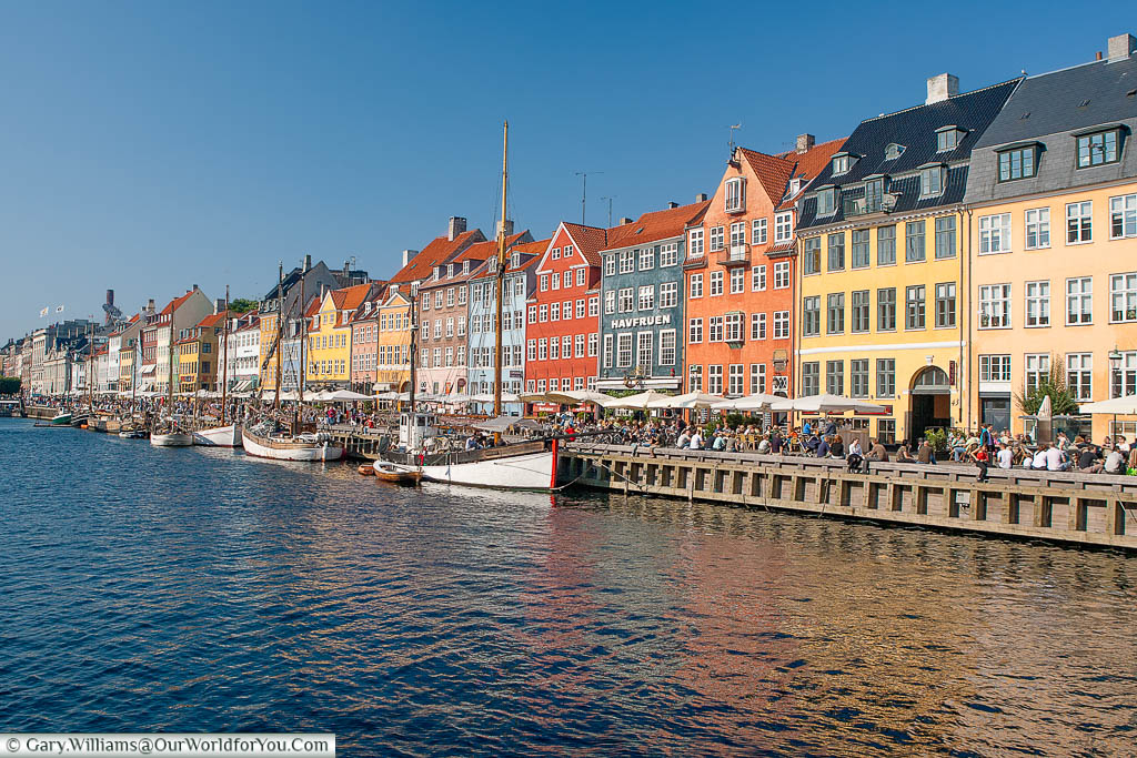 Boats in front of the multi-coloured buildings and home to so many bars & restaurants in Nyhavn, Copenhagen, Denmark