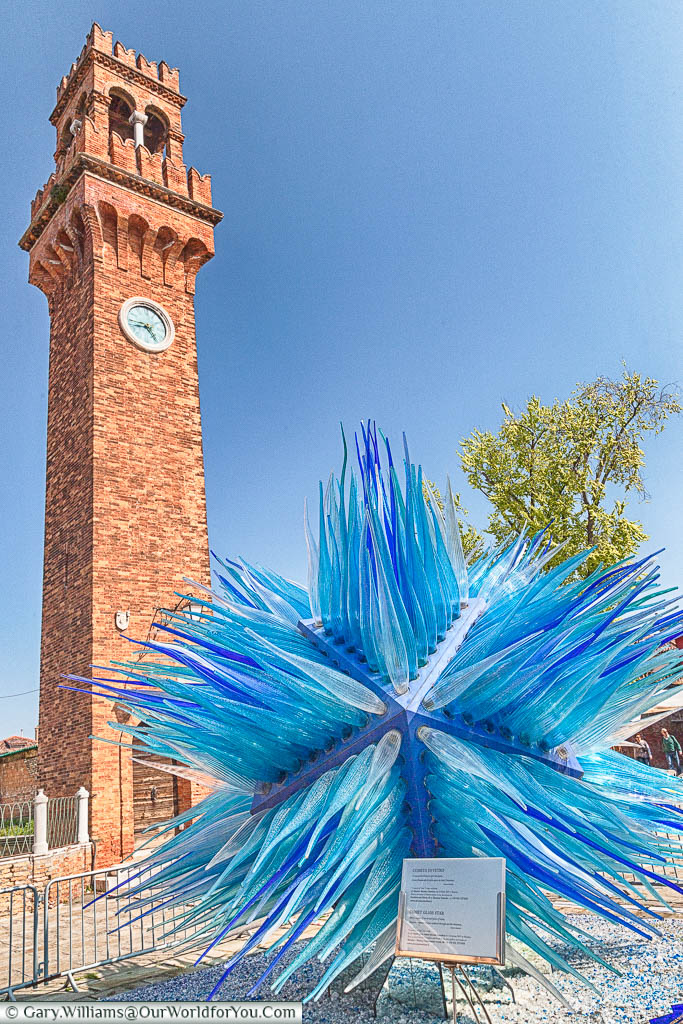 A 2-metre blue glass comet sculpture at the base of a historic Venetian clock tower.  This installation can be found on the island of Murano, a short water bus ride from Venice.