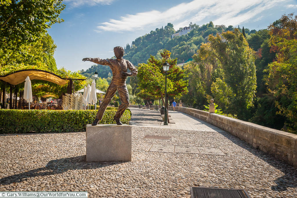A statue to Mario Maya, a renowned male flamenco dancer, against the  backdrop of the hills surrounding Granada.