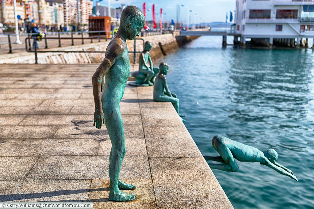 A collection of four bronze statues, coloured verdigris, on the water's edge depicting young boys diving into Santander's natural harbour.