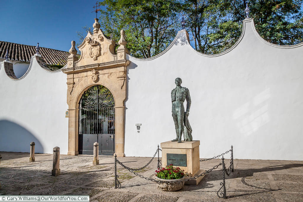A statue to a matador, in front of the walls that surround Ronda's bullring.