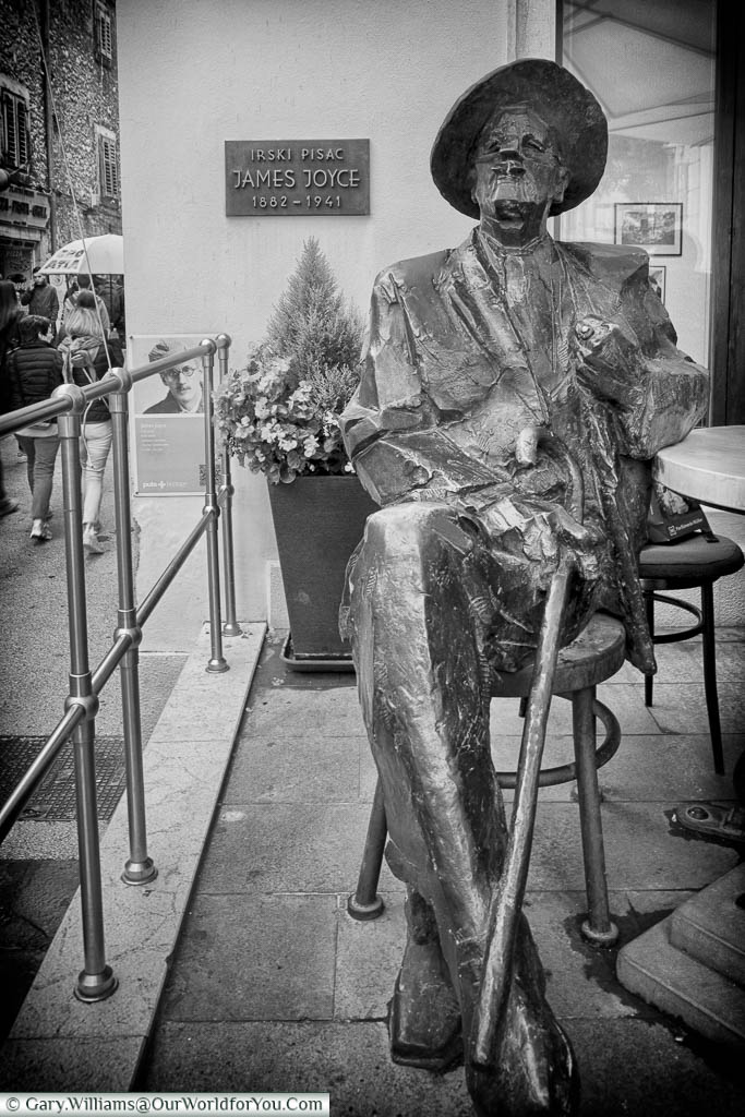 A black and white shot of a seated statue to the Irish novelist James Joyce outside a cafe in Pula, Croatia