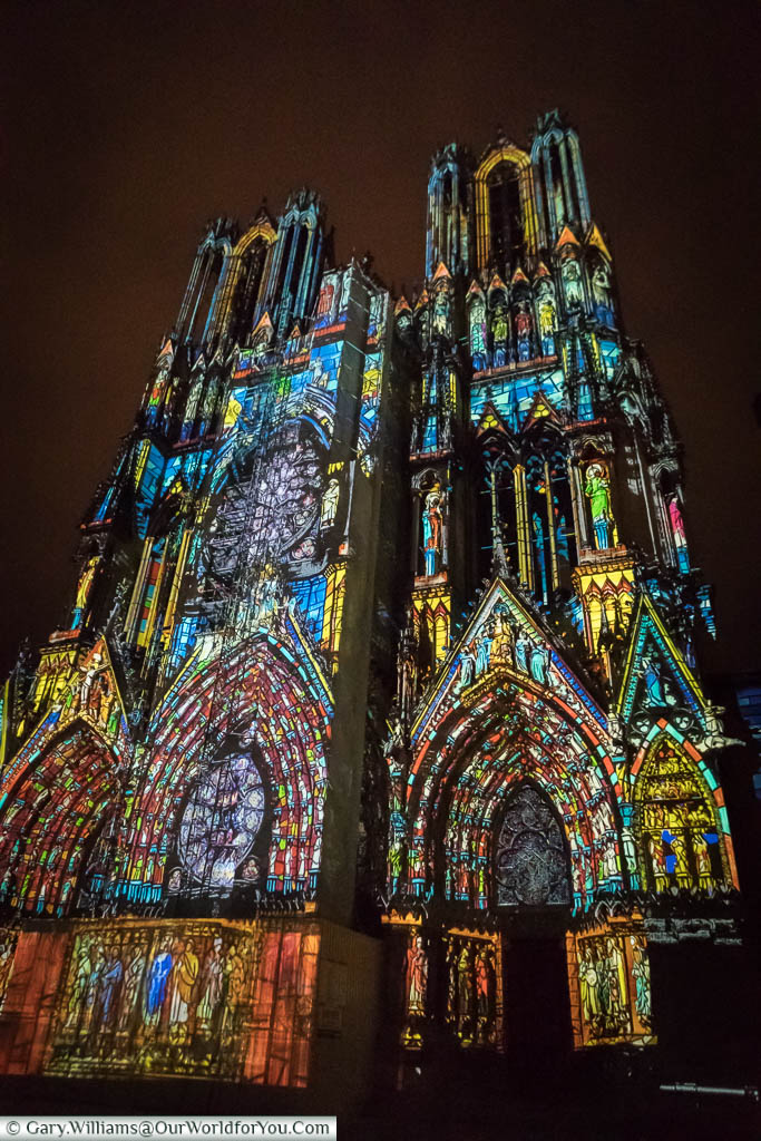 The entrance to Reims Cathedral at night, with a projected art installation depicting the history of this French City