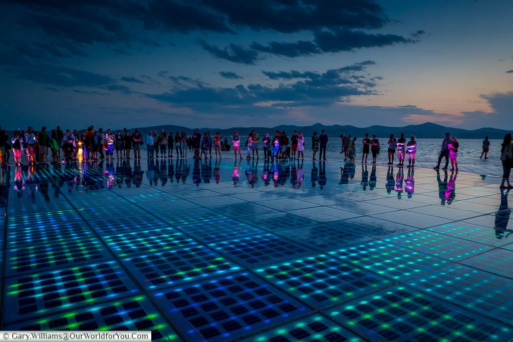People gather around the 'Greeting to the Sun' light display at Zadar's Riva at dusk.  They are illuminated by the LED floor tiles that make up this open-air art installation.