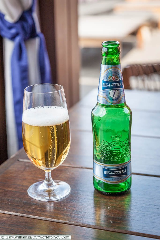 A glass of cold Baltika Beer next to its green bottle.  A local beer in Saint Petersburg, Russia