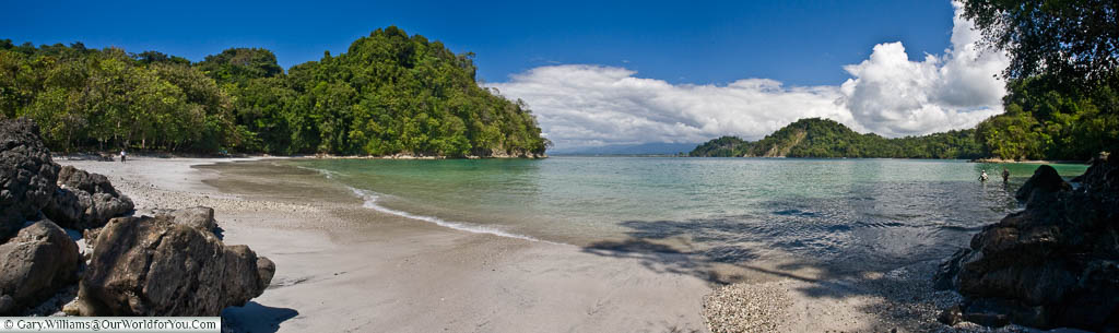A panoramic view over the sandy, isolated, beach of Playa Biesanz, Manuel Antonio, Costa Rica.  Surrounded by the lush green vegetation that Costa Rica is renown for.