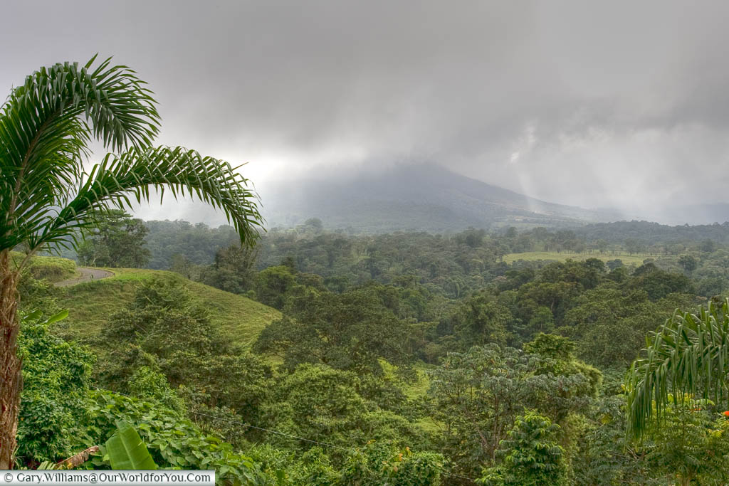 A view of the Arenal volcano, shrouded in cloud, across the lush landscape of Costa Rica.