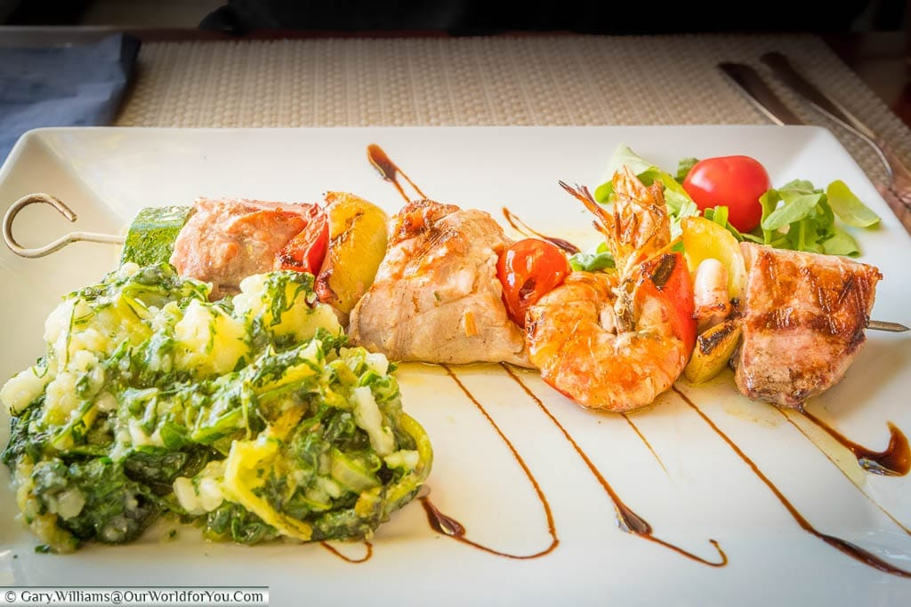 A fish skewer served with potatoes & greens, a light salad on a white rectangular plate.