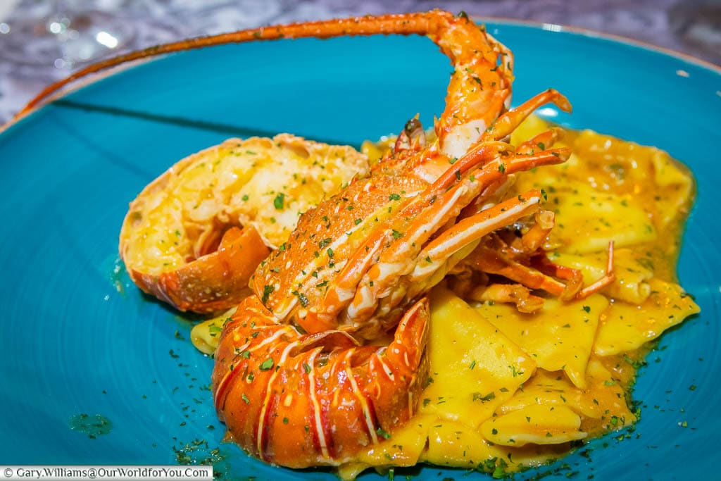 """A large langoustine on a bed of Ravioli on a blue plate at the Restaurant """"Bon Appetit"""""""