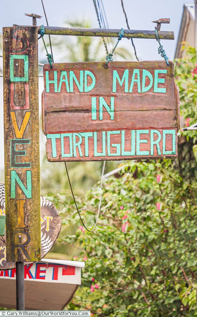 A rustic sign offering 'Hand Made  in Tortuguero' souvenirs next to a shop in the backwaters of Tortuguero, Costa Rica