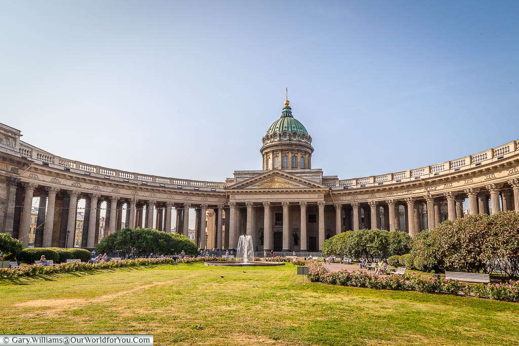 Looking across the lawn in front of the Kazan Cathedral, also known as the Cathedral of Our Lady of Kazan, in Saint Petersburg, Russia.  With its outstretched curved colonnades, it is said to resemble St. Peter's Basilica in Rome.