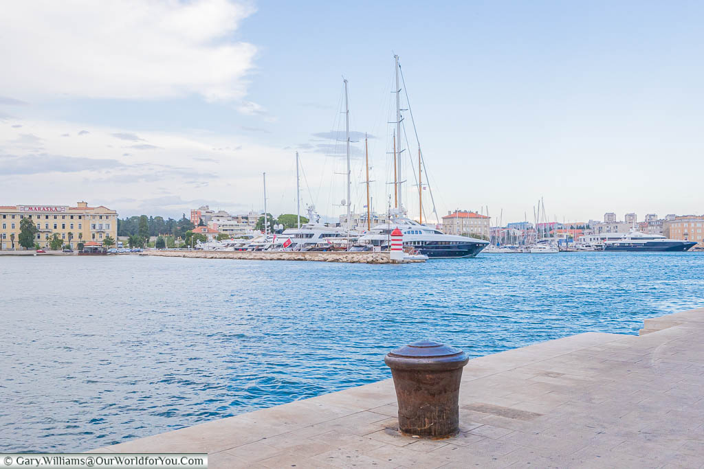Standing on the marina side, with expensive, superyachts and tall sailing ships moored up, overlooking the ancient city of Zadar, Croatia