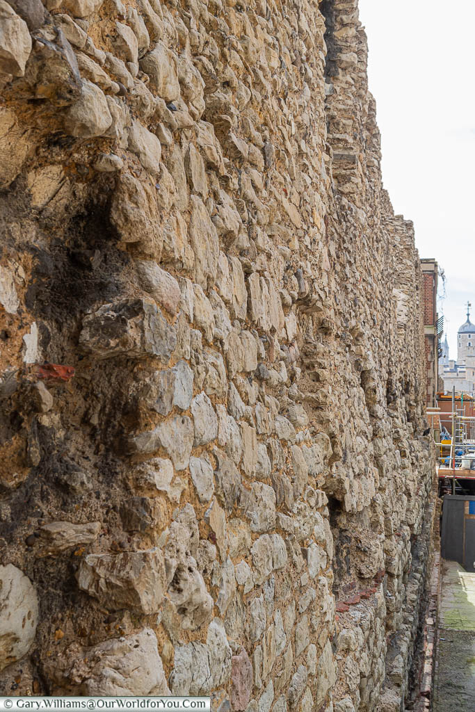 A close-up view of an exposed section of London's Roman wall, with the Tower of London just visible in the background.