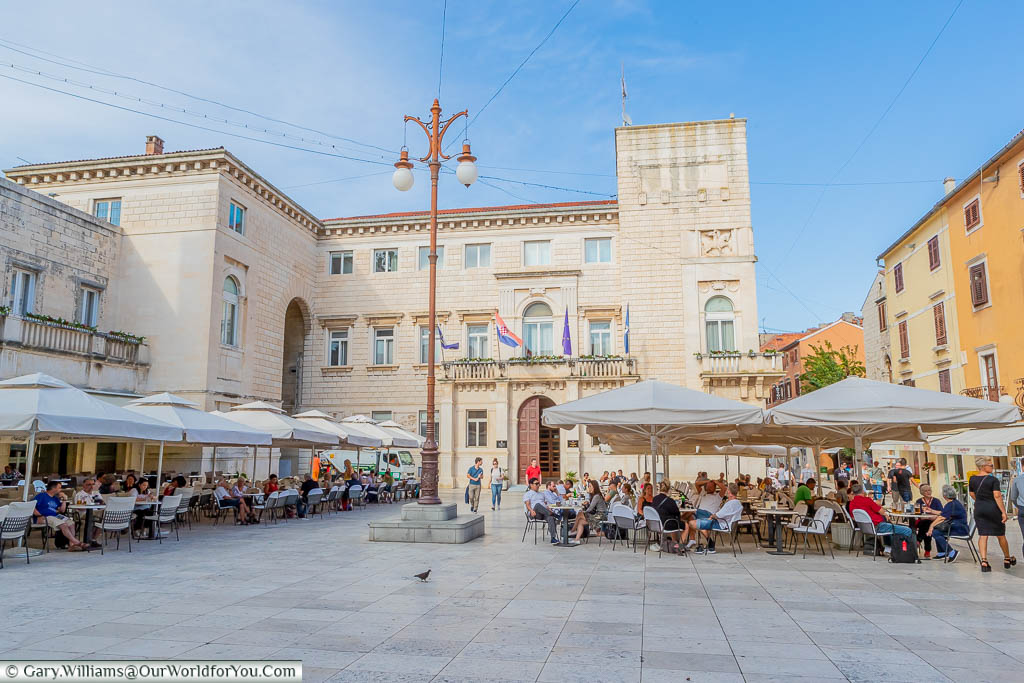 Families sitting at tables under parasols in People's Square in the old town of Zadar