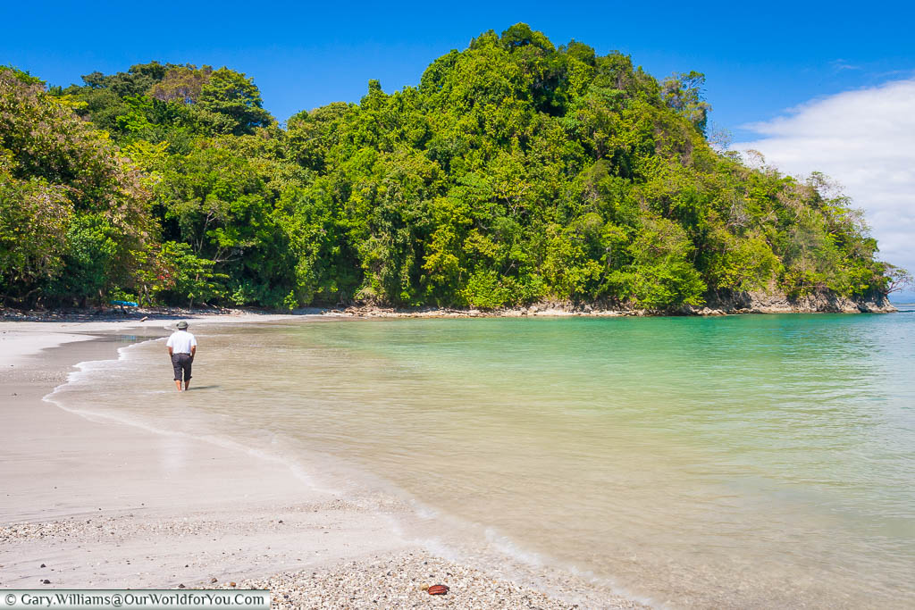 A lone figure strolling on the beach at Playa Biesanz, in a bay in Manuel Antonio, on the Pacific side of Costa Rica.