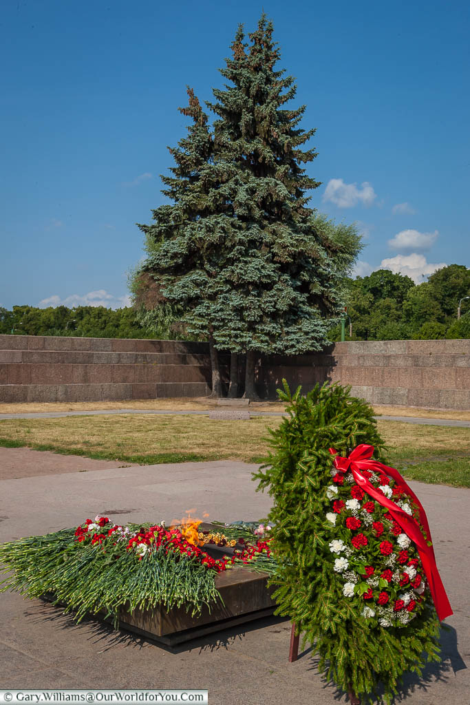 A wreath, decorated with red & white flowers, stands before the Eternal Flame in the Field of Mars, St Petersburg, Russia.
