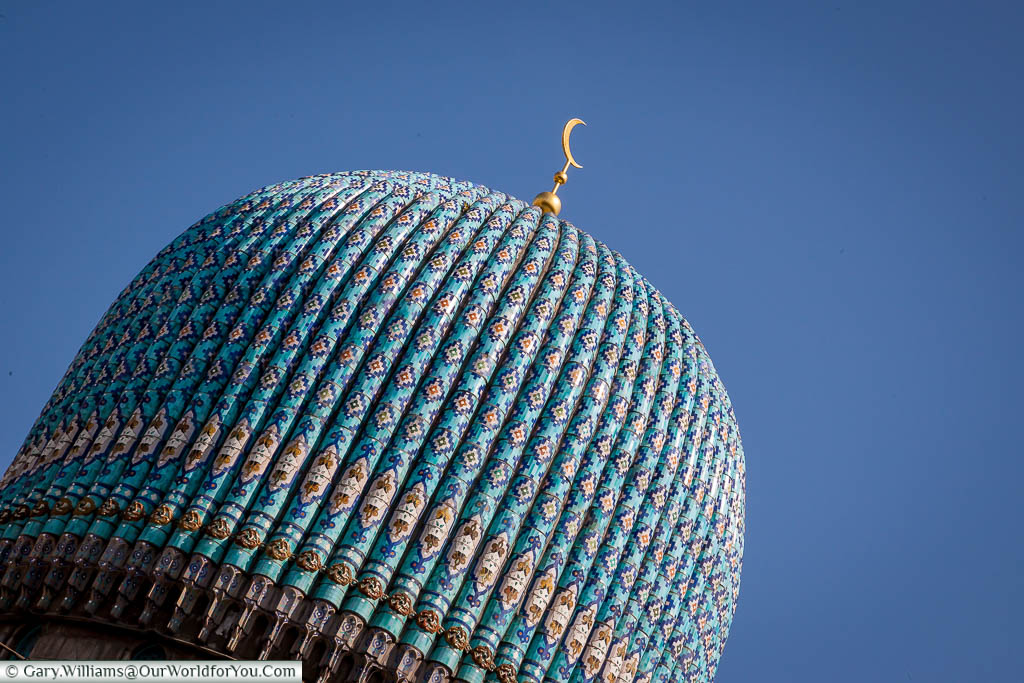 The tiled dome of the Great Mosque of Saint Petersburg in Russia.  The surface is covered with mosaic ceramics of sky-light-blue colour and topped with a golden crescent.
