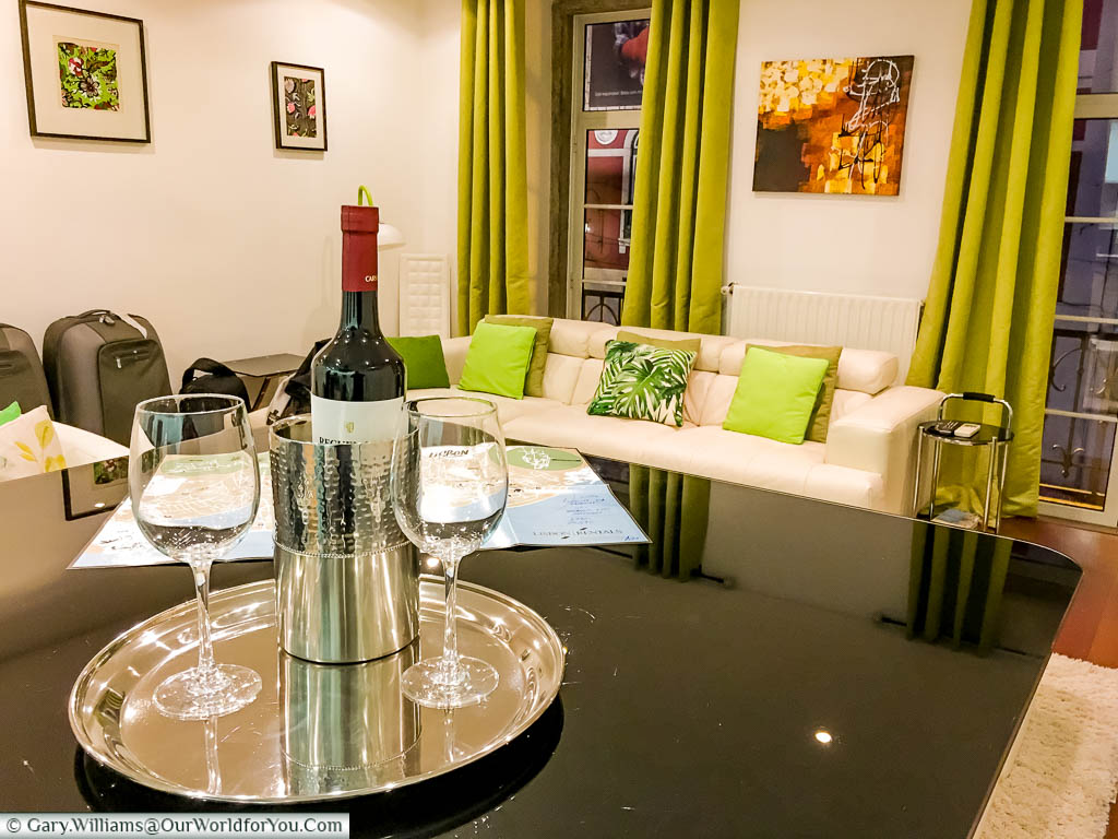 A bottle of wine in an ice bucket with two glasses on the breakfast bar of our apartment with Lisbon Rentals Chiado in Lisbon, Portugal