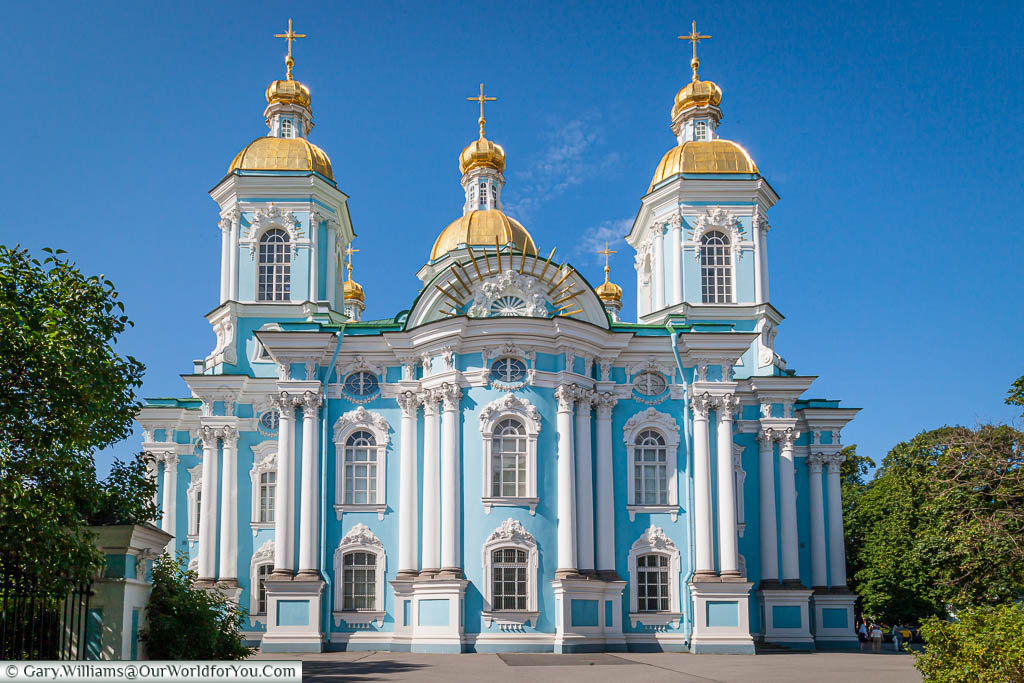 The front of the Saint Nicholas Naval Cathedral in Saint Petersburg, Russia.  The church is predominately powder blue, with white columns and is crowned by five gilded domes.