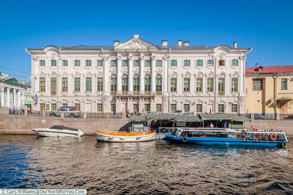 Boats moored up in front of the Stroganov Palace on the banks of the Moyka River, Saint Petersburg, Russia