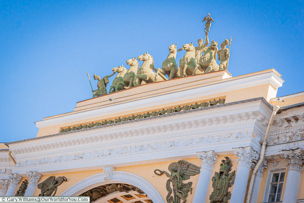 The top of the Triumphal arch, focusing on the detail on top with a Roman chariot of 6 horses surging forward.  The Triumphal arch leads onto Palace Square in Saint Petersburg, Russia