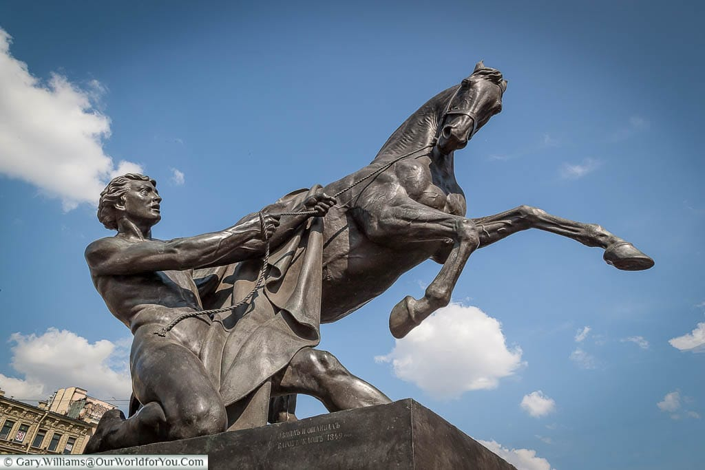 The second Horse Statue on the Anichov Bridge depicting the trainer kneeling as he tries to bring the beast under control.