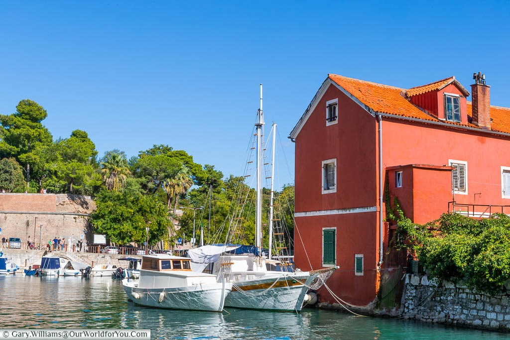 Two white sailing boats mooring in the small picturesque port of Fosa in Zadar.