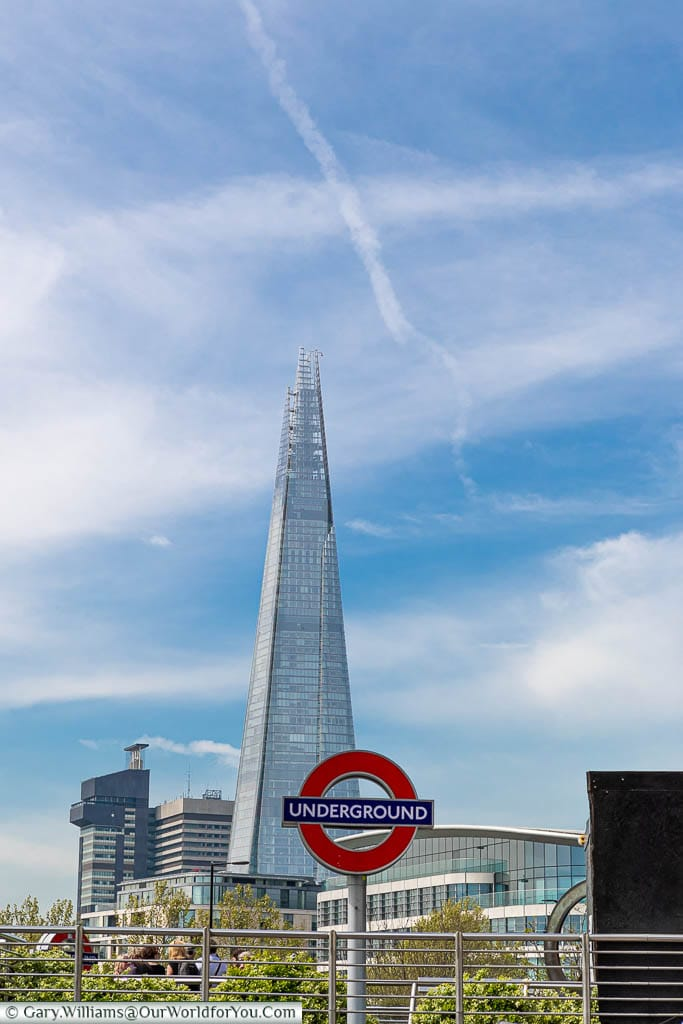 The London Underground sign at Tower Hill tube station, on a bright sunny day with the Shard in the background.