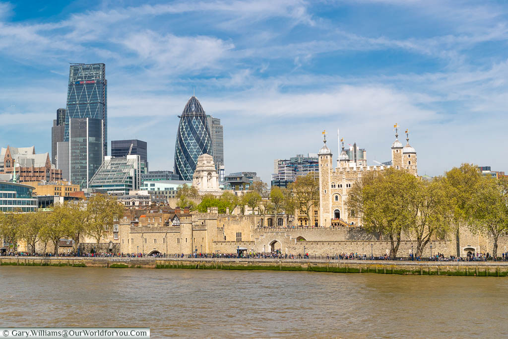 A view of the Tower of London from Tower Bridge with the River Thames in the foreground, and nestled next to the Tower of London are the skyscrapers of the City of London.