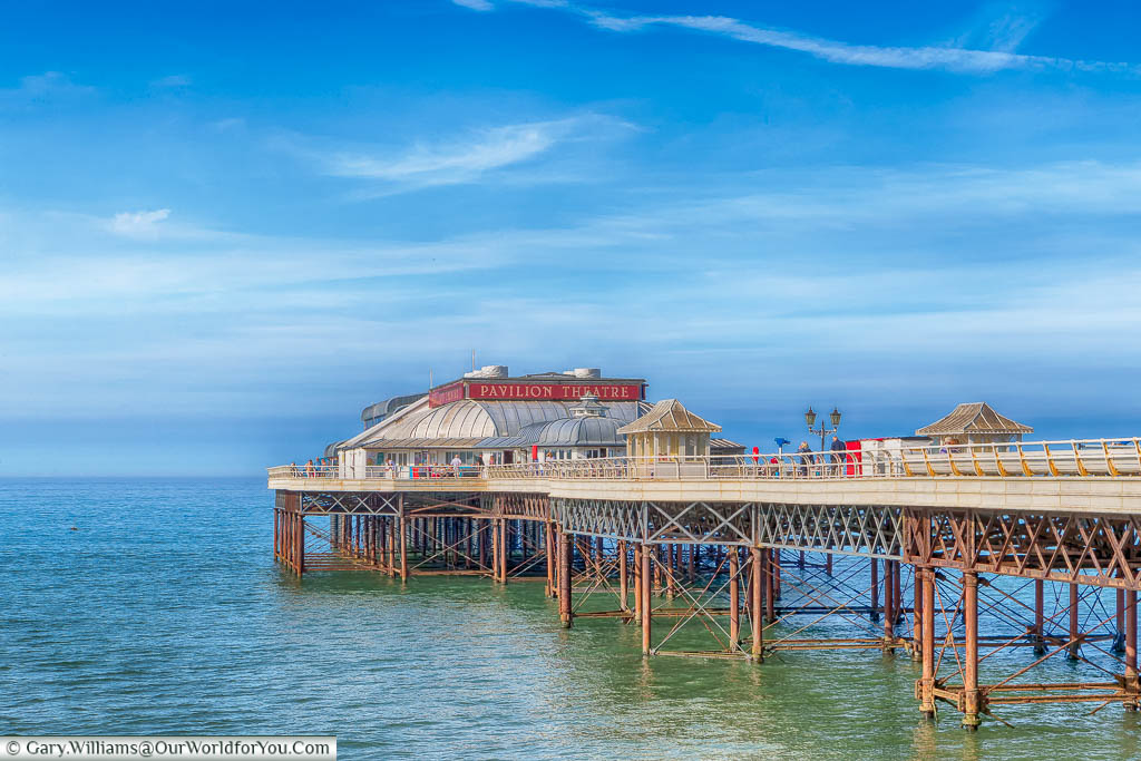 An off-centre view of Cromer Pier from the coastal path on a beautiful sunny day with blue skies.  You can clearly see the wrought-iron framework and the Pavillion Theatre at the end