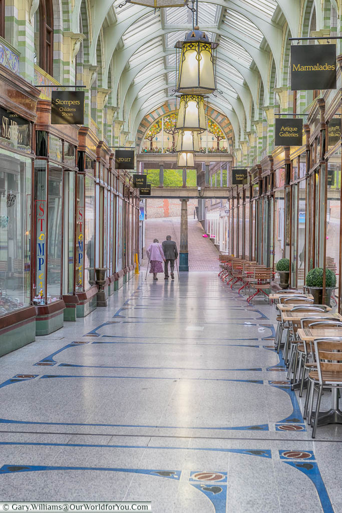 Inside the Art Deco Royal Arcade in Norwich, with its pretty mosaic tiled floor and lanterns suspended from an iron and glass vaulted ceiling.