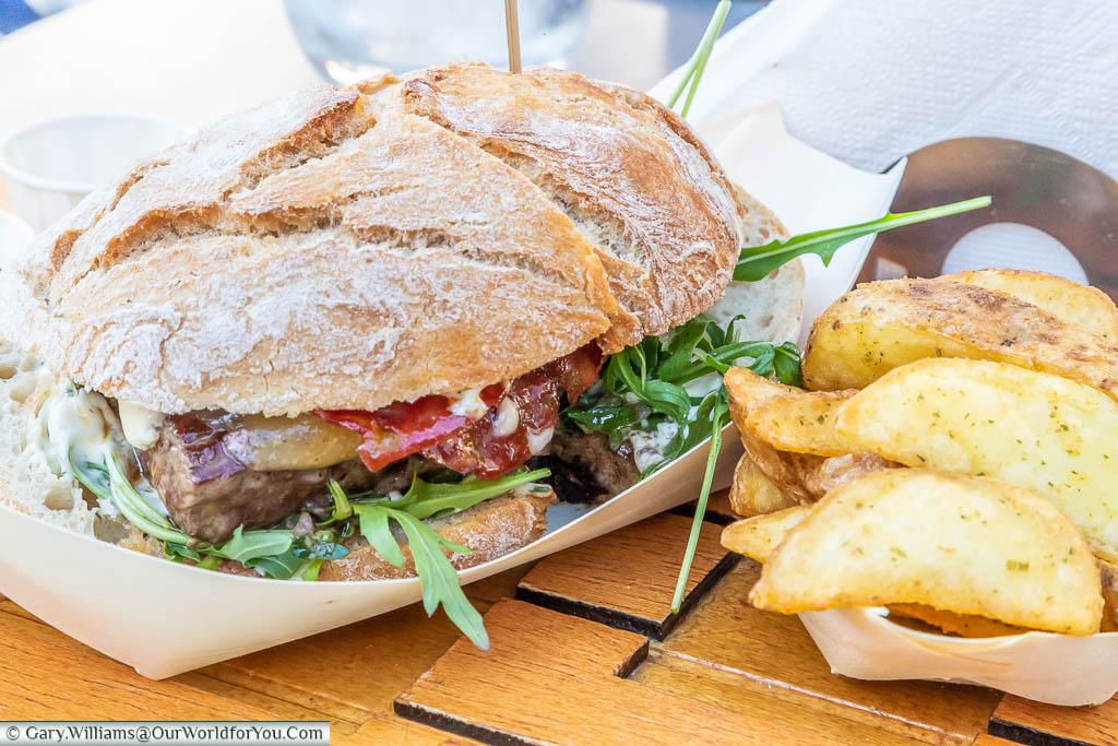 A prego, a Portuguese steak sandwich, served with a side order of potato wedges, at a table outside a cafe in Guimarães