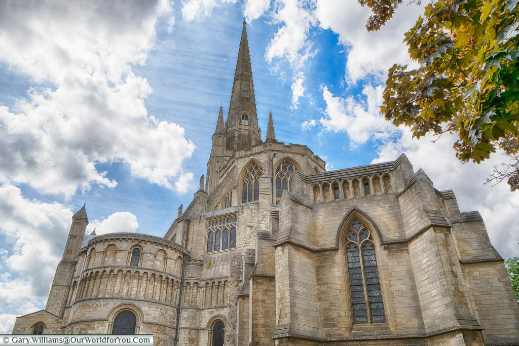 Looking up at the spire of Norwich Cathedral as beams of light appear from the partially cloudy sky