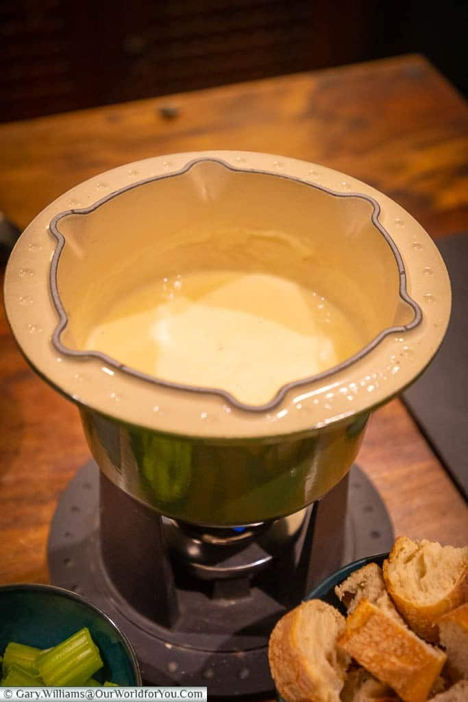 Our cast iron fondue pot, half-filled with a bubbling cheese fondue, with a pots of chopped celery & cubed french bread