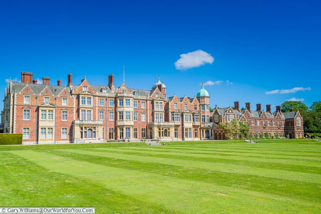 The rear of Sandringham House across the well-manicured lawns, under blue skies, on a beautiful day in Norfolk.