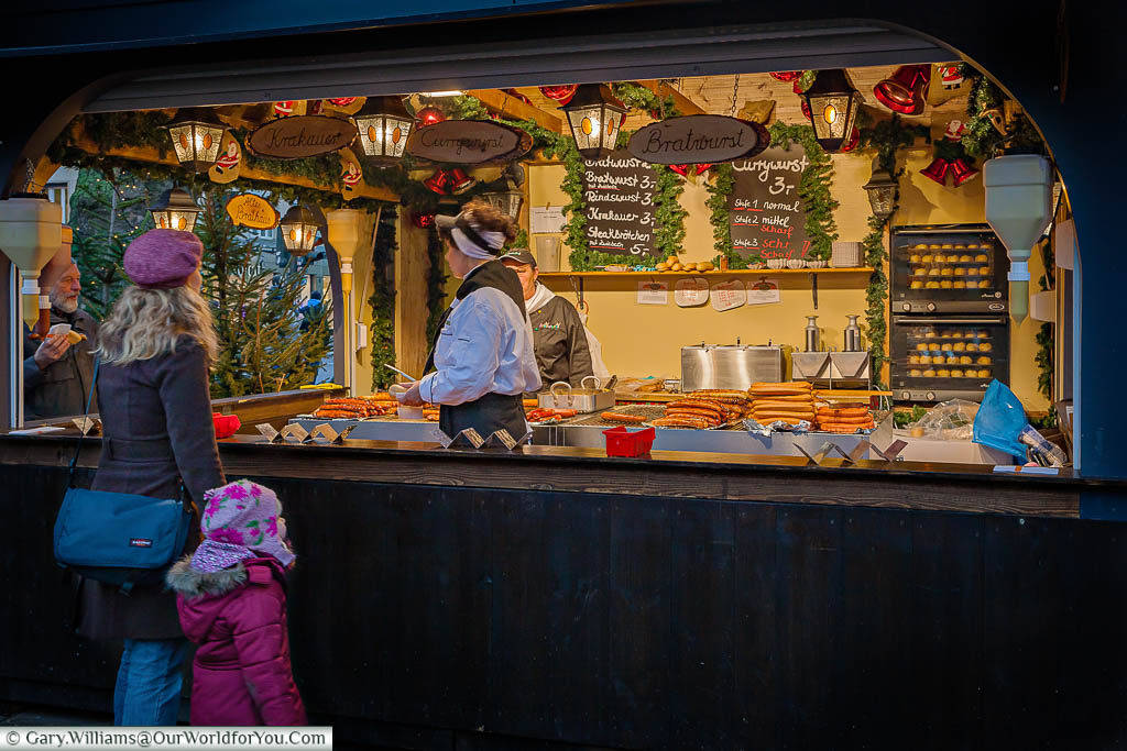 A mother and young girl at a sausage stall at the Cologne Christmas market