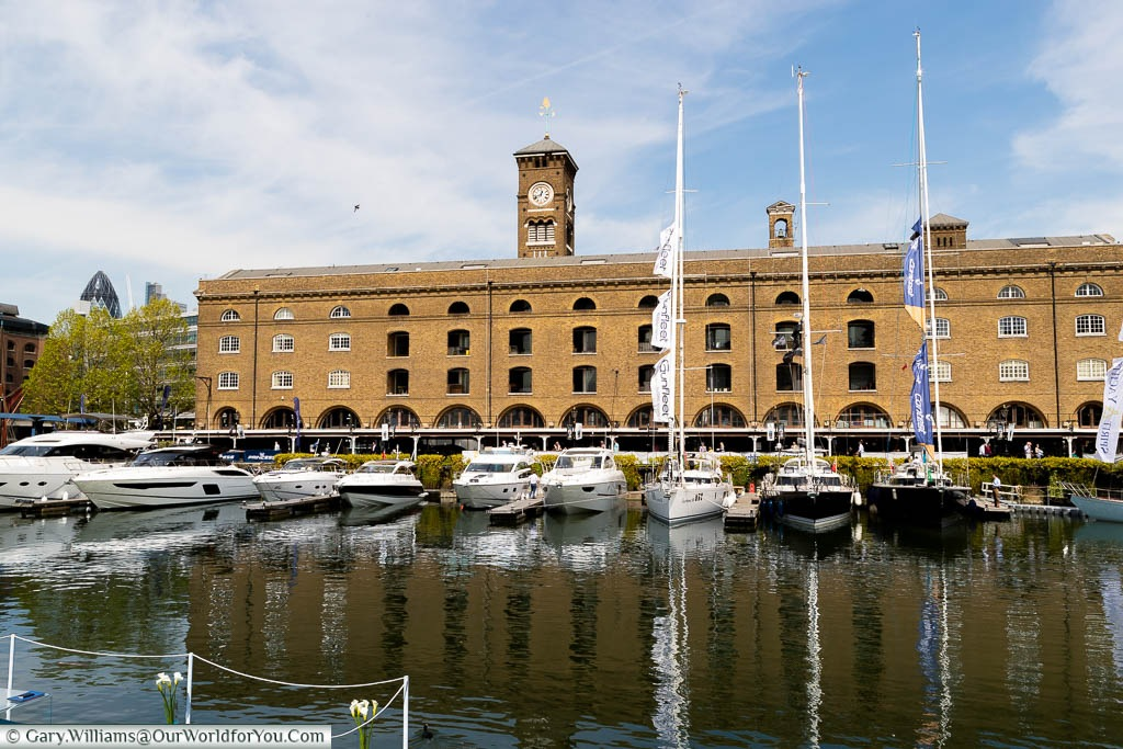 The Saint Katharine Docks in London, next to Tower Hill, with small, luxury, private boats moored in front of a historic warehouse building.