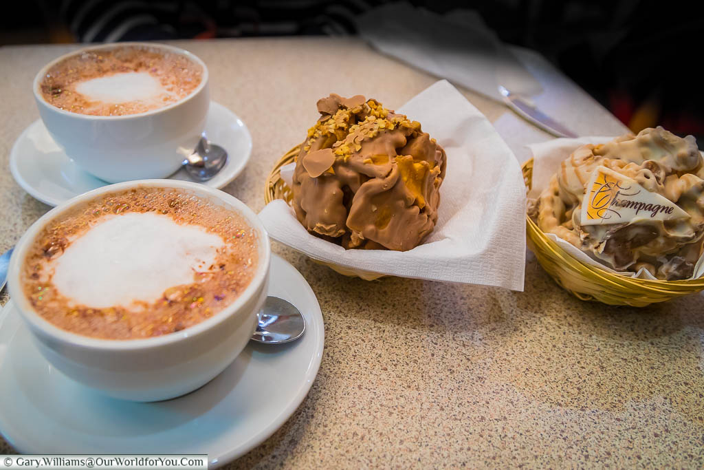 Two cups of hot chocolate to accompany the two chocolate covered schneeballen biscuit balls the size of a snow ball.