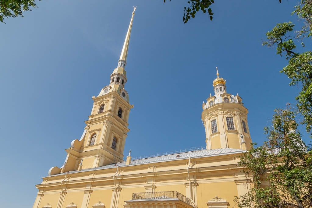 The side profile of the mustard yellow Cathedral, topped with a narrow gold spire, and shorter dome,  in Saint Petersburg, Russia
