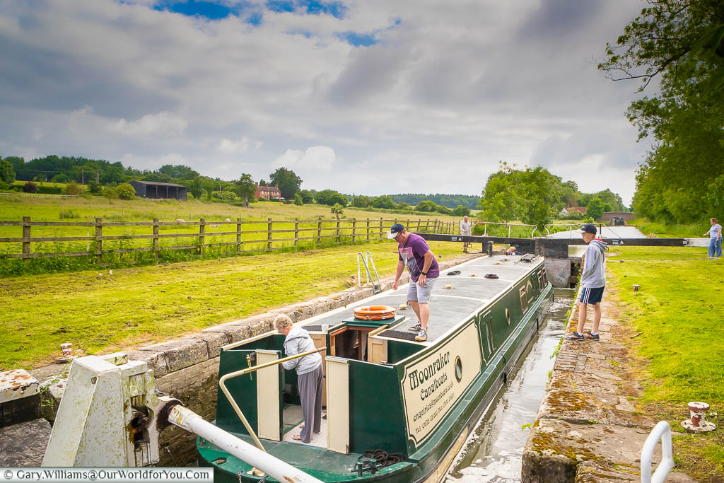 Three generations involved in taking a wide beam narrowboat through a lock on the Kennet & Avon canal