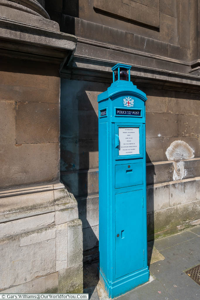 A brightly painted mid-blue Police post public call box next to a stone building