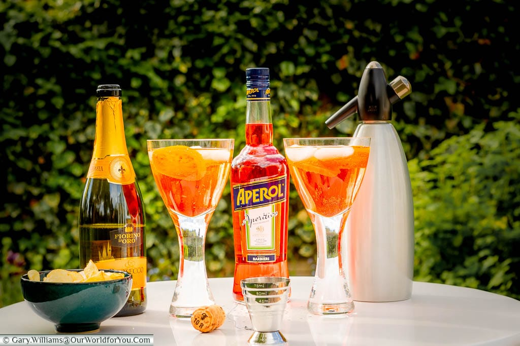 Two glasses of Aperol Spritz with a bottle of Prosecco, a bottle of Aperol, a soda syphon and a bowl of crisps in our garden