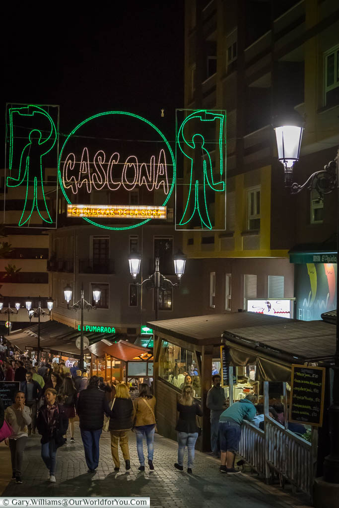 Groups of people strolling along Calle Gascona, Oviedo, Spain at night.  The Street of Cider is lined with bars on both sides serving the local tipple