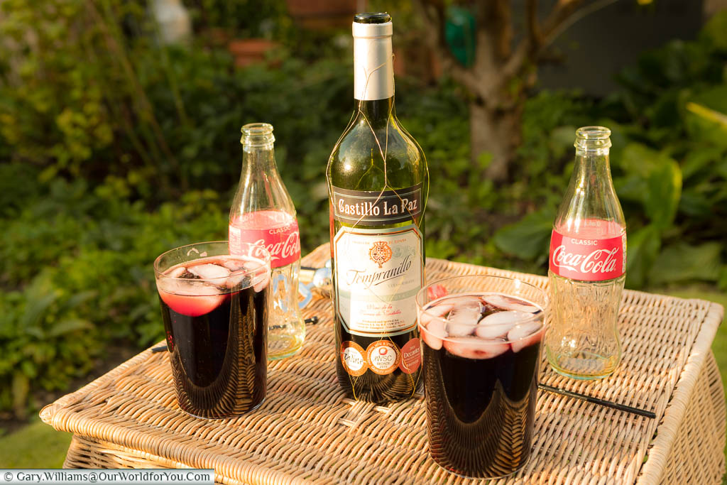 Two large straight glasses of homemade Calimocho on a wicker table in our garden in Kent, Egland