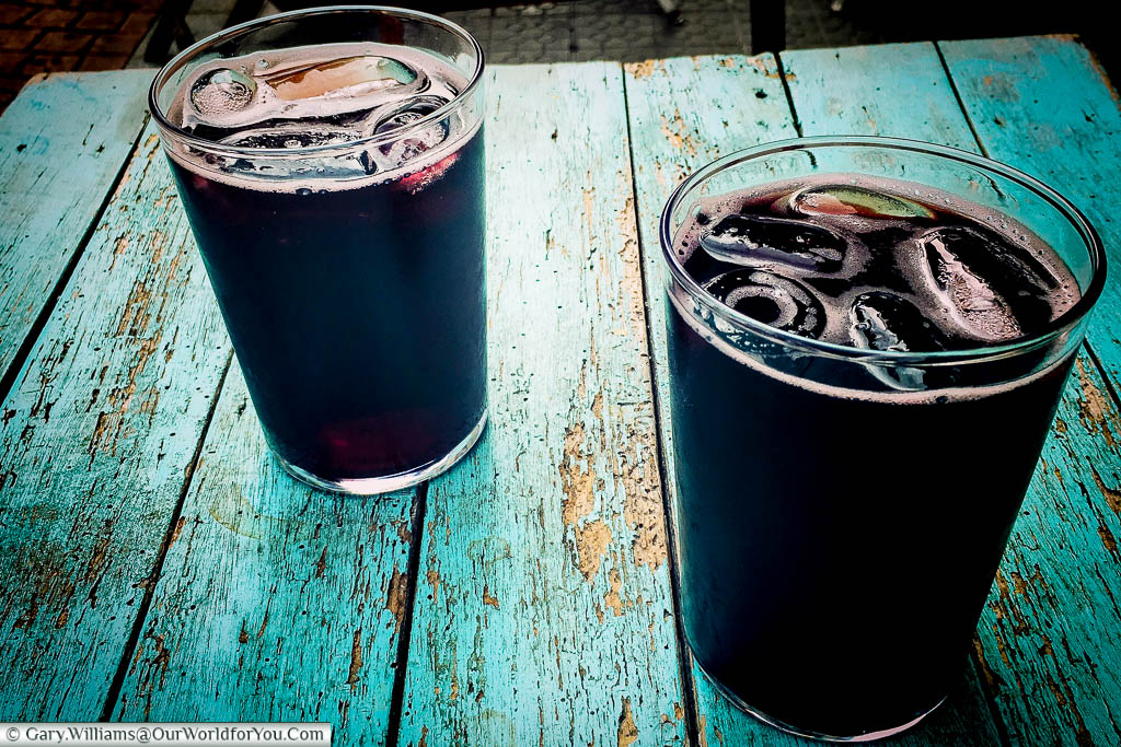 Two large straight glasses of Calimocho on a distressed table outside a bar in Bilbao, Spain