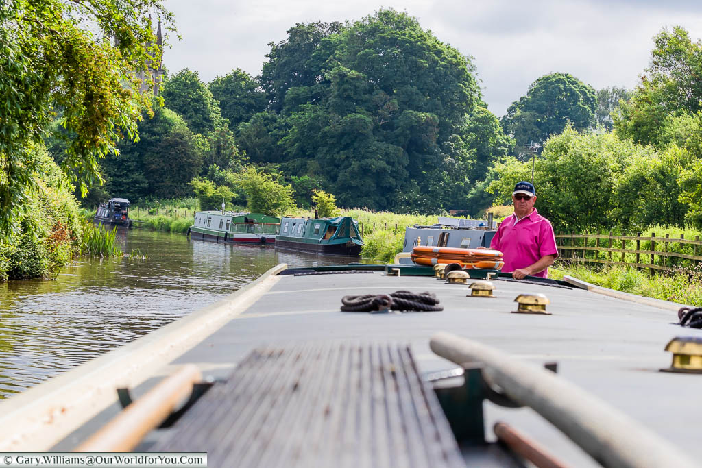A shot along the length of the narrowboat to the skipper guiding the boat along the canal