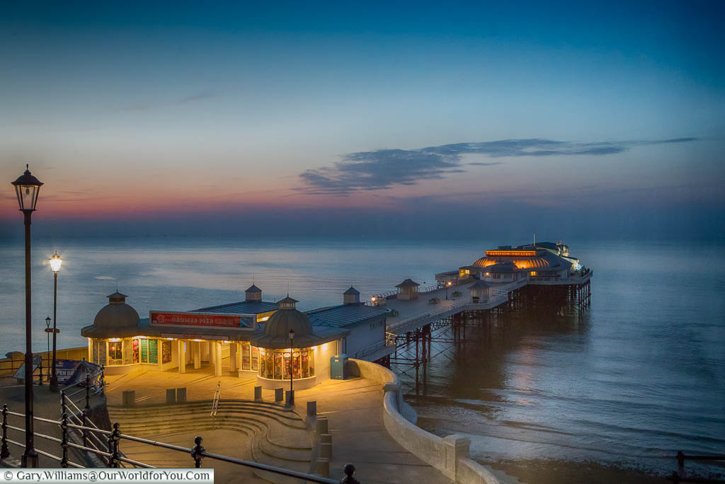 A view of the illuminated, elegant, Cromer Pier, after dusk, under orange and blue hues.