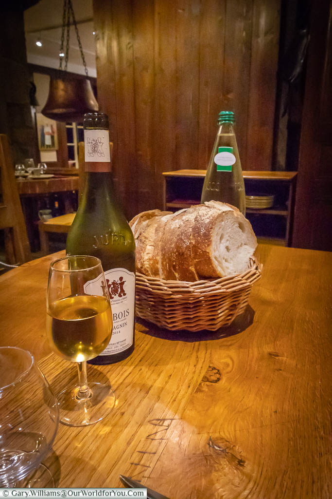 A glass of the vin jaune next to a basket of bread in Arbois, France