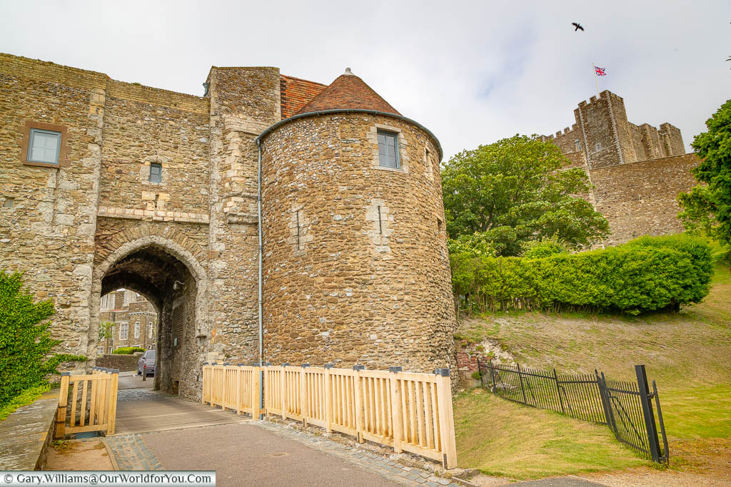 A stone gatehouse at Dover Castle with the Keep high on the hillside